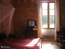 De ruime 2e persoons slaapkamer met oude Franse meubelen kijkt uit op de boomgaard.