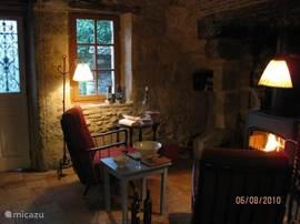 In de comfortabele stoelen in de woonkeuken kun je om de haard zitten.