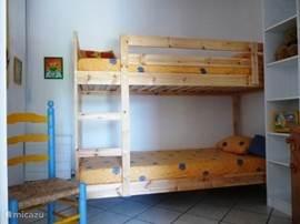 Slaapkamer op de benedenverdieping met stapelbed.