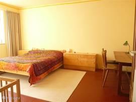 grote slaapkamer(20m2) met tweepersoonsbed aan de kant van de beek Kledingkast, tafel en stoelen. Kinderledikantje.