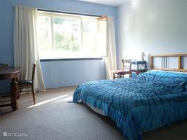 De blauwe slaapkamer(21m2), met kledingkast en tafel met stoelen