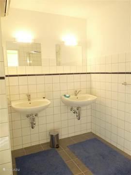 Eén van de twee ruime en heldere badkamers met douche en 2 wastafels.