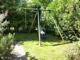 Rond om de bungalow loopt de tuin, voorzien van een speeltoestel