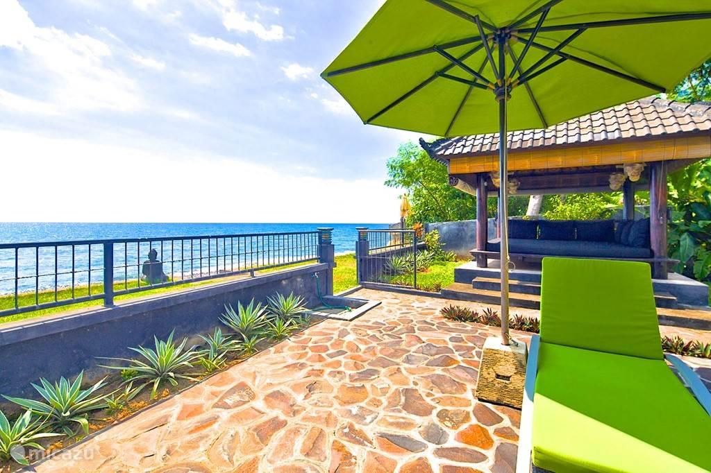 terras met loungeplek met dikke kussens direct aan het strand