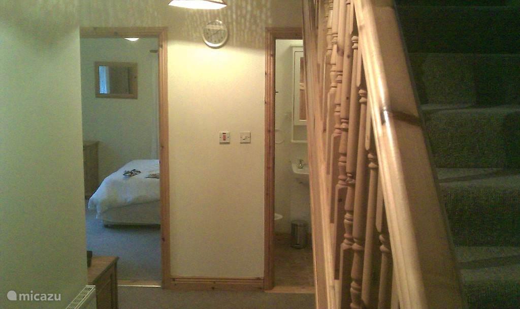 hier ziet men een deel van de tweede slaapkamer op de begane grond en een deel van de badkamer (wc en douche) in de gang beneden.