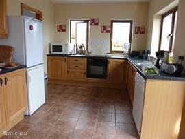De ruime keuken met openslaande deuren naar de tuin is van alle apparatuur voorzien. Vanaf de aanrecht heb je aan twee kanten uitzicht.