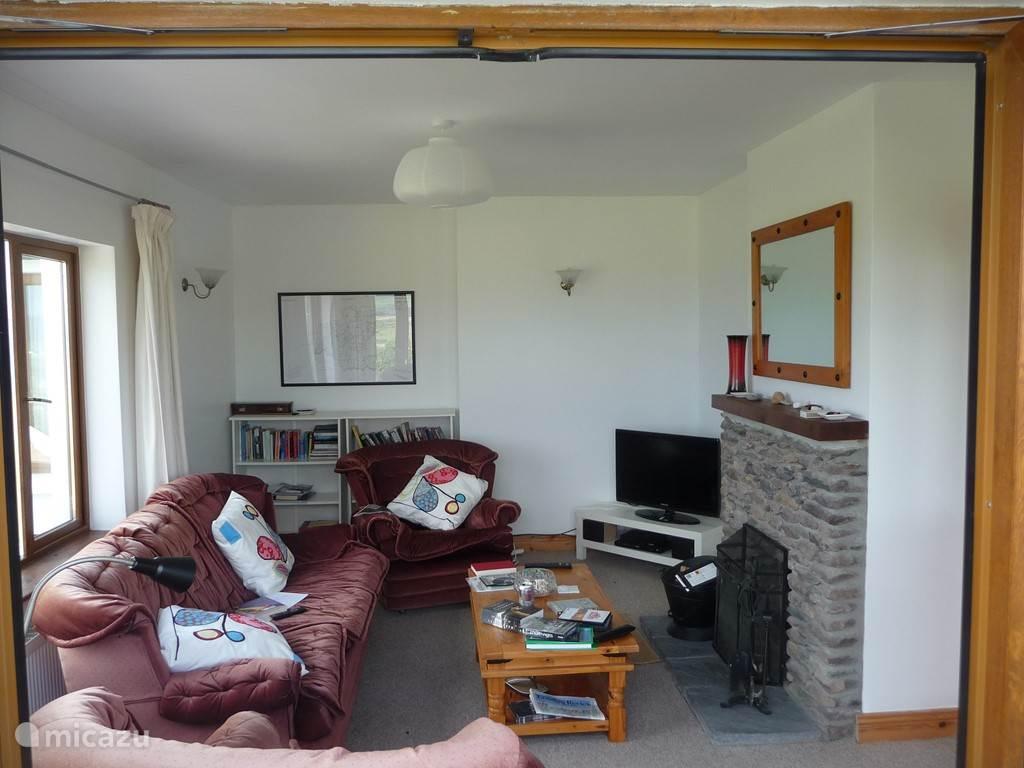 De zitkamer met open haard en televisie. De open haard wordt begin 2015 door een kachel vervangen die het nog warmer en knusser moet gaan maken.