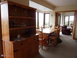 De eetkamer vanaf te keuken te zien met uitzicht op de zitkamer.