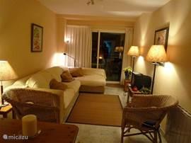 Zithoek met tv en schuifdeuren naar het balkon