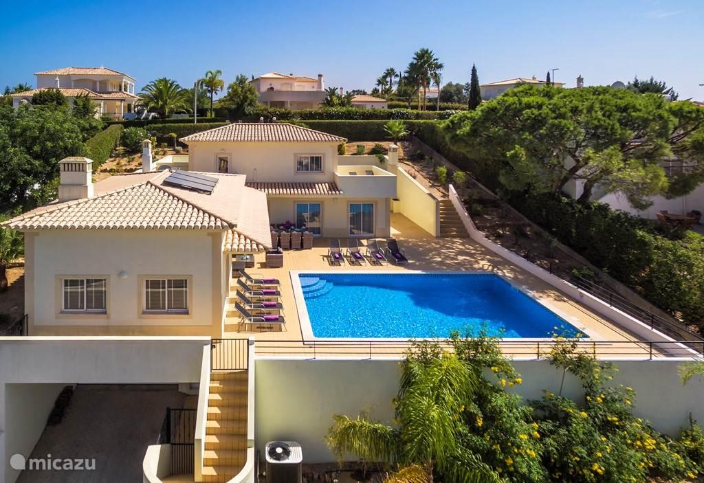 Achterzijde: Aangelegde tuin met rondom het verwarmde zwembad een ruim zonneterras. In de ruime lounge hoek is het gezellig borrelen. Een vers visje op de originele Portugese BBQ en het vakantiegevoel is compleet.  Vanaf het terras heeft u een prachtig uitzicht over Carvoeiro.
