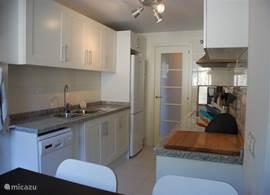 Aanzicht vanaf eettafel naar de ruime en moderne keuken.