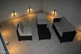 Het gezellige en ruime dakterras met sfeerverlichting en een 4 persoons lounge set.
