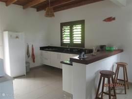 Zeer moderne zwevend opgehangen L.Keuken voorzien van granieten aanrechtblad met 4 pits kookplaat.  Mooi hardhouten plafond en deur naar achterkant van de tuin. Verder voorzien van alles wat in een keuken nodig is.