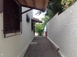 Zijkant woning van wasplaats naar grote terras en tuin.
