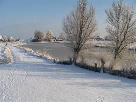 Winters uitzicht vanuit het huis op het water en het dorpje Schardam.