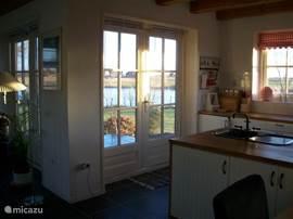 Vanuit de open keuken bereik je via openslaande deuren direct het zonnige terras.met eettafel waar je heerlijk kan zitten.