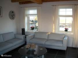 De woonkamer met zithoek. Door elk raam een ander, uniek uitzicht.