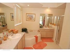Master bathroom. Deze badkamer ensuite heeft 2 wastafels, een apart toilet, aparte ruime douche en een groot hoekbad.