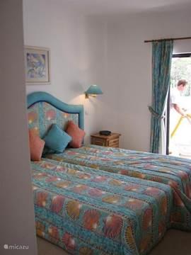 De ruime hoofdslaapkamer met badkamer en suite, inbouwkasten en een schuifpui naar het terras