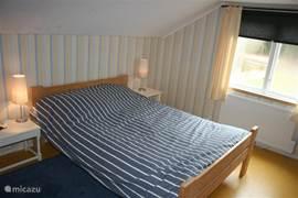Slaapkamer met een 2-persoons bed en een 2 persoons slaapbank.