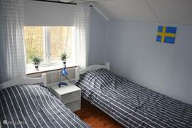 Slaapkamer met 2 eenpersoonsbedden en een PS2 en een tv met dvd.