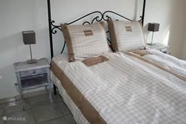 Fraaie tweepersoons slaapkamer met smeedijzeren hemelbed.
