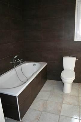 De comfortabele en-suite badkamer met ligbad, toilet, hydromassage doucecabine, wastafel en verwarmd handdoekenrek.