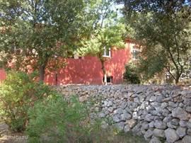 Zijaangezicht van de villa vanuit de achterzijde van de tuin.