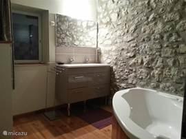 Vernieuwde badkamer met een ruim hoekbad (en douche), ideaal voor kleine kinderen.