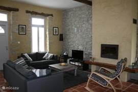 Een karaktervolle living met open haard en een comfortabele open keuken.
