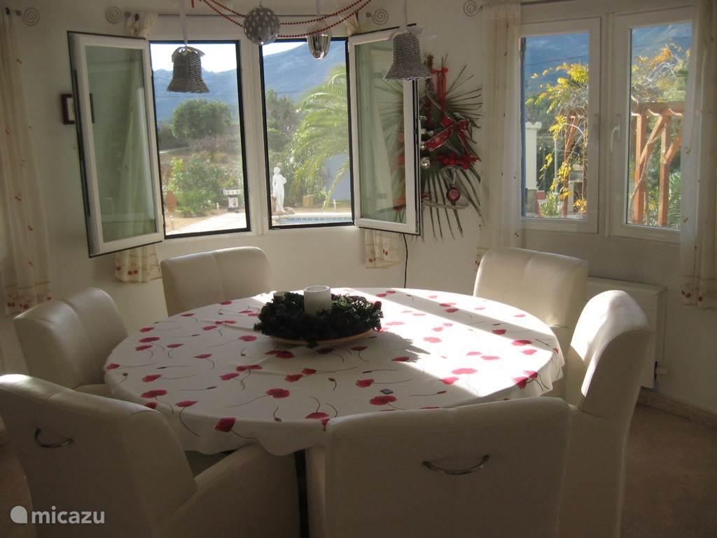 gezellige ronde eetkamer met uitzicht op de tuin, het zwembad en de bergen