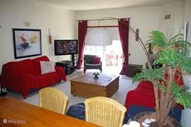 Ruime woon-eetkamer met 3 and 2 zits sofa. Eettafel met 6 stoelen en televisie met Nederlandse en Portugse kanalen.