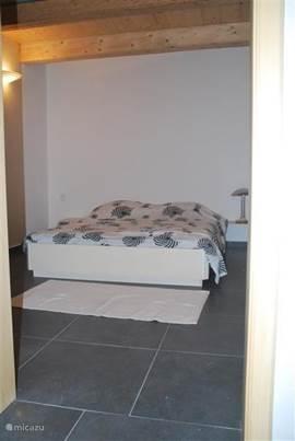 Slaapkamer beganegrond met 2-persoonsbed en aangrenzende badkamer