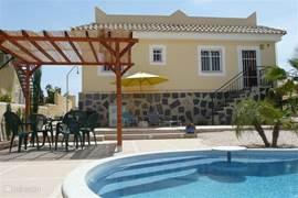 In de ruime achtertuin bevind zich het achterterras en het ruime zwembad. Hier kunt u heerlijk genieten van de zon en een verkoelende duik in het zwembad nemen.