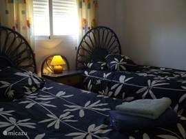 Deze slaapkamer heeft 2 eenpersoonsbedden en beschikt over een inbouwkast.