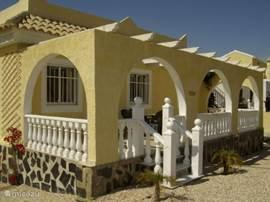 Vooraanzicht op het voorterras van Casa Camposol. Het voorterras beschikt over een groot zonnescherm.