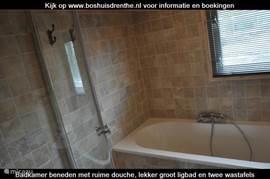De eerste badkamer beneden is prachtig afgewerkt en beschikt over een ligbad,  twee wastafela en een heerlijke ruime douchecabine.