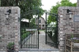 Toegang tot onze tuin. Achterin de tuin bevindt uw vakantiewoning zich. Voor het hek beschikt u over een eigen parkeerplaats.