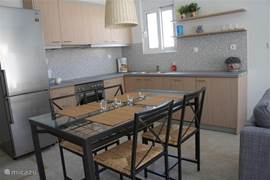 The kitchen has a large dining table. There is a fridge-freezer, oven, ceramic hob, kettle, dishwasher and hood.