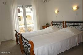 The spacious bedroom has two single beds (90X200), air conditioning and a large wardrobe. There are also doors to the terrace overlooking the pool and the sea.