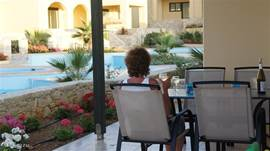 From the private terrace has sea view. The pools are two steps down, the access is closed by a low fence. There is a large dining table with four chairs. Sun beds and chairs are also in the pool area.