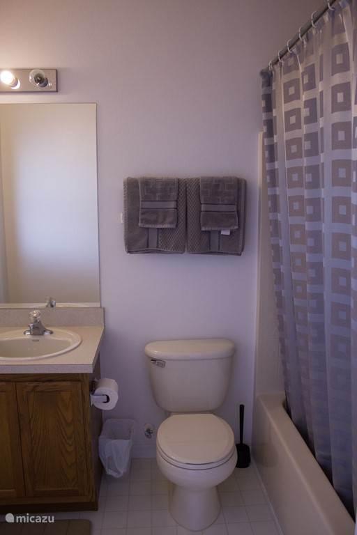 Badkamer 1. behoort bij master bedroom 1. voorzien van een enkele wastafel, toilet en ligbad met douche. Tevens bevind zich hier een deur naar het terras/ zwembad.