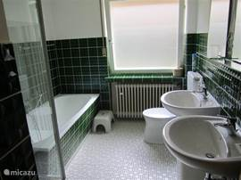 The bathroom on the first floor with bath, shower, toilet and double sink.
