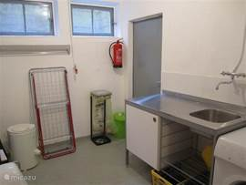 The laundry room on the ground floor with washing machine, spin dryer, clothes horses and bins for paper, glass etc.