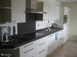 De keuken van het gastenverblijf is van alle gemakken voorzien.  Vaatwasser, oven/magnetron, inductie kooplaat, koelkast en diepvrieskast.
