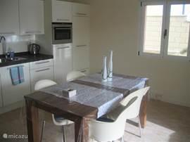 De keuken van het gastenverblijf is voorzien van schuifdeuren naar het terras.