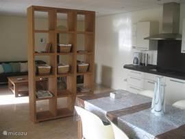 De keuken van het gastenverblijf is gescheiden van de woonkamer door een roomdivider.  De keuken en woonkamer zijn voorzien van airco.
