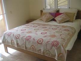 De hoofdslaapkamer van het gastenverblijf met een 2 persoons bed  met schuifdeuren naar het overdekte terras. Voorzien van airco.