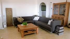 De gezellige woonkamer met hoekbank van de boven woonlaag. De woonkamer is gescheiden van de keuken door middel van een gashaard.   De woonkamer is voorzien van airco.
