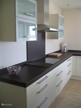 De hoekkeuken van de villa. Deze is van alle gemakken voorzien, zoals keramische kookplaat, vaatwasser, koelkast, diepvries, oven/magnetron, koffiezetapparaat, waterkoker en compleet voorzien van servies, bestek e.d.